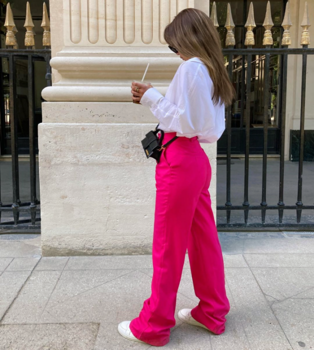 light haired girl wearing white dress shirt, fuchsia pink pants, white tennis shoes, small black leather bag