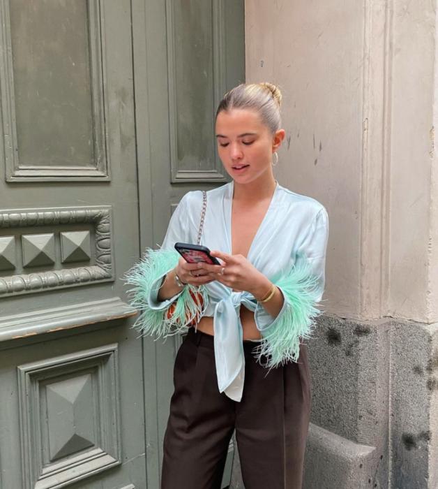 chica de cabello rubio usando una blusa celeste con plumas en las mangas, pantalones cafés holgados de vestir