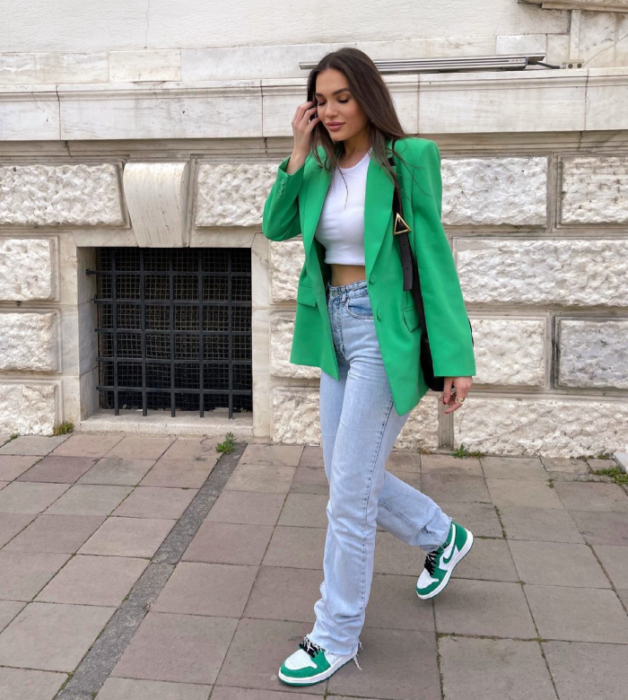 brown haired girl wearing a white crop top, bright green blazer, light blue skinny jeans, white with green and black tennis shoes, black bag