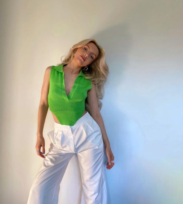 chica rubia con top verde brillante con escote en V, pantalones de vestir blancos
