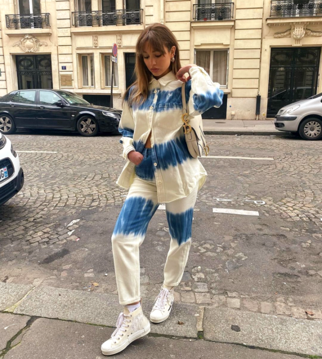 light haired girl wearing blue denim shirt with beige horizontal stripes, blue baggy pants with beige horizontal stripes, white low top sneakers