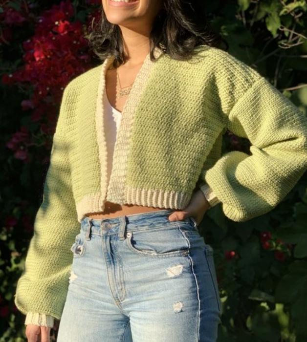 chica de cabello oscuro con top blanco, cárdigan verde pistache, jeans ajustados