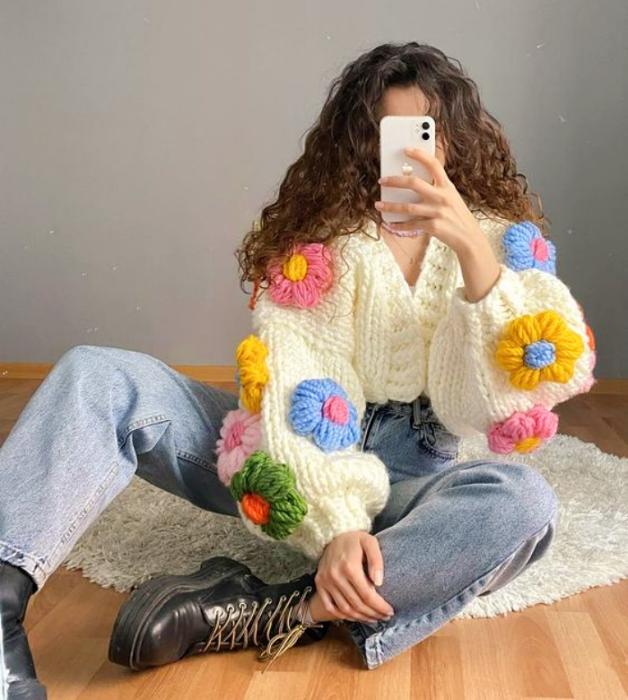 chica de cabello chino usando un cárdigan beige con flores grandes rosas, azules, amarillas y verdes, jeans holgados y botines negros de cuero
