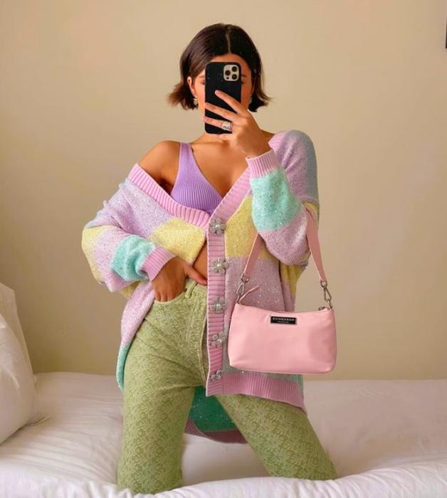 chica de cabello corto oscuro con top morado, cárdigan lila con amarillo y azul celeste, pantalones verdes claros y bolso pequeño rosa pastel