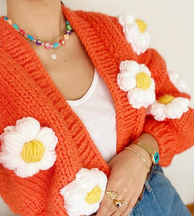 cárdigan naranja brillante con flores blancas grandes, top blanco, jeans ajustados