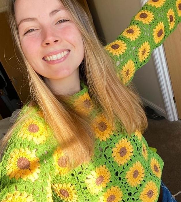 chica rubia con suéter tejido verde limón con flores amarillas y jeans ajustados