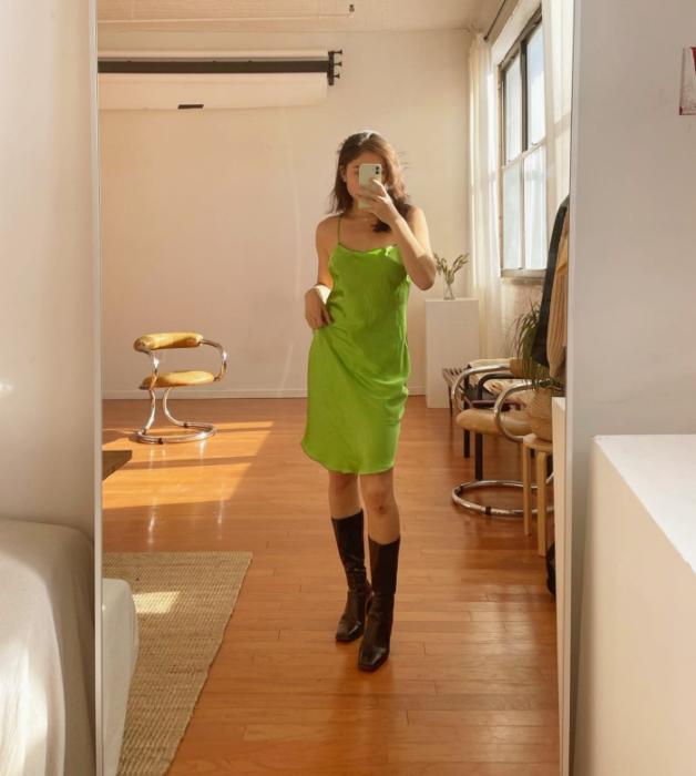 chica de cabello castaño usando un vestido de satén verde de tirantes con botas largas negras de cuero