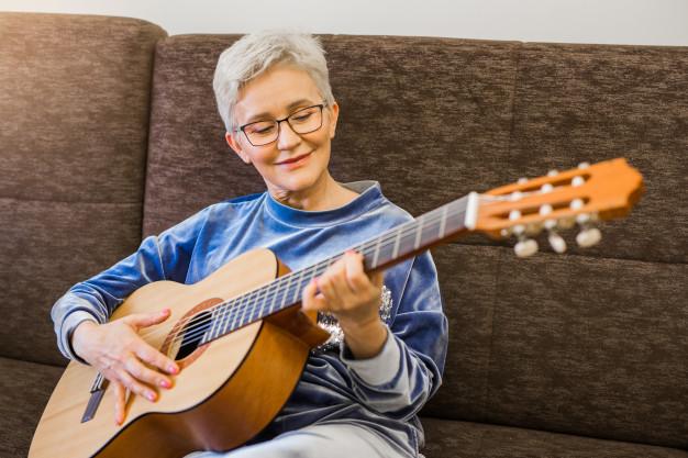 mujer tocando la guitarra ;13 Regalos chulos y originales para sorprender a mamá en su día