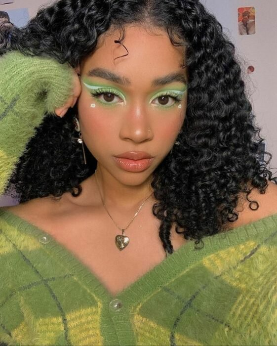 brunette girl with eye makeup on green grass with pearl decoration; 15 makeup in green tones to reconnect with nature