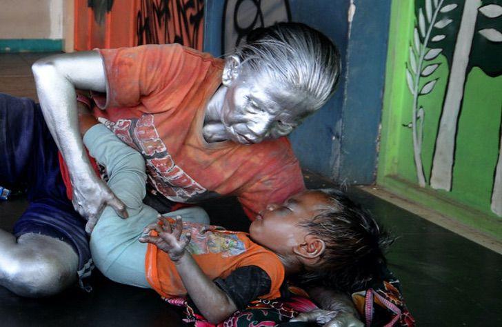 Abuelita que trabaja como estatua recostando a su nieto en una cama