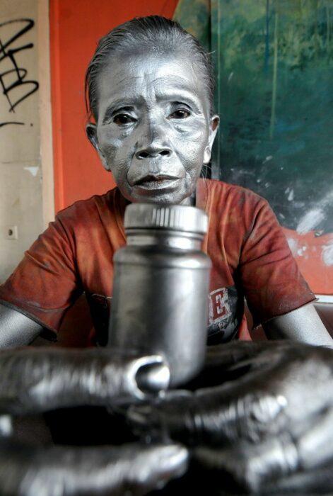 Abuelita con el rostro pintado de plateado para trabajar como estatua en las calles
