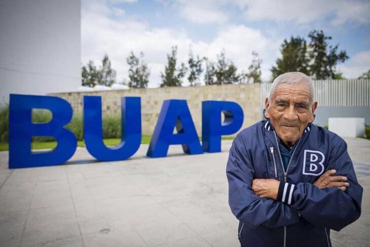 Abuelito de 84 años que se graduó de Ingeniero posando frente a la universidad