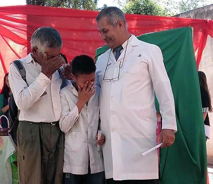 Abuelito y nieto llorando tras recibir su diploma en la escuela; Abuelo y nieto rompen en llanto recibiendo su diploma. Caminaron 6 km a diario hasta la escuela