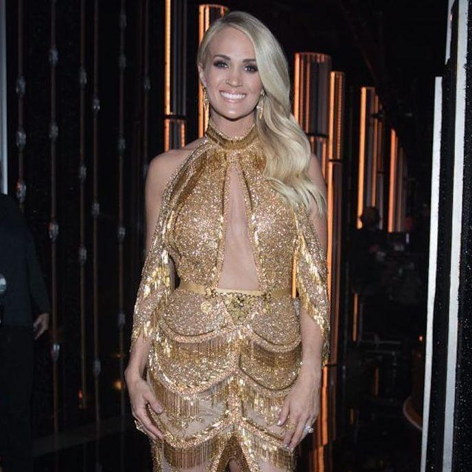 Carrie Underwood usando un vestido dorado con flecos