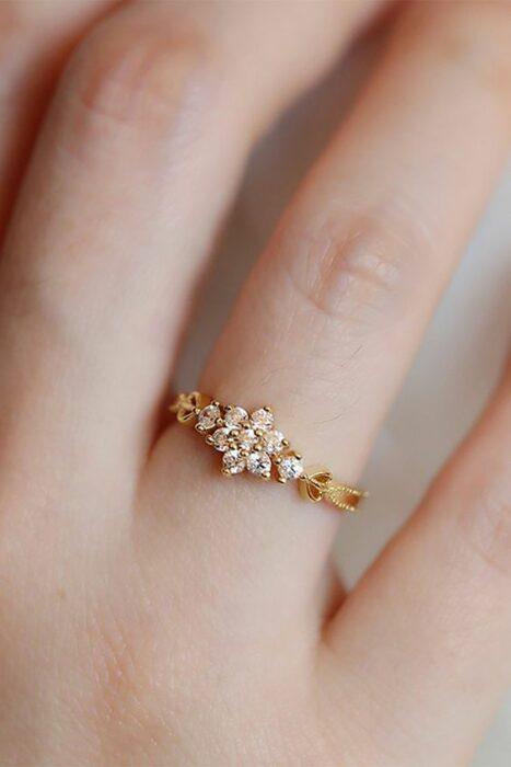 Anillo de compromiso en tono dorado con una piedra color transparente