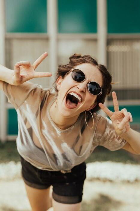 chica haciendo señas y sonriendo ;Así es como afecta el estrés a tu salud bucal y no lo sabías