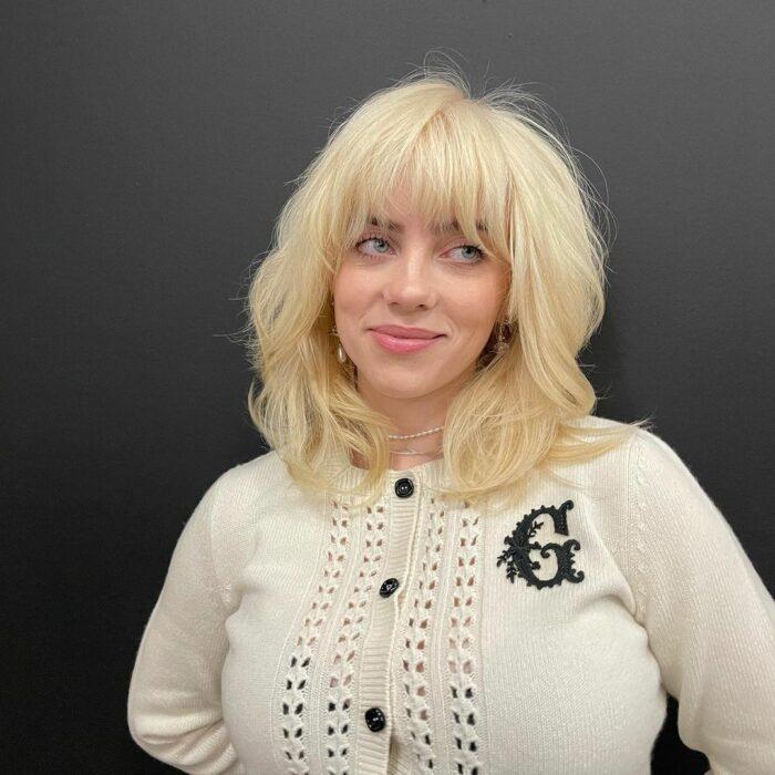 Billie Eilish posando para una foto mientras muestra su look rubio