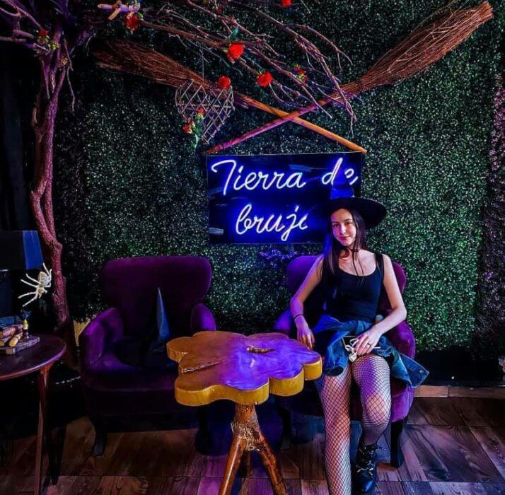 Chica sentada dentro de Salem Witch Store & Coffe; ;Esta cafetería inspirada en brujas sirve las mejores posiciones del mundo oscuro