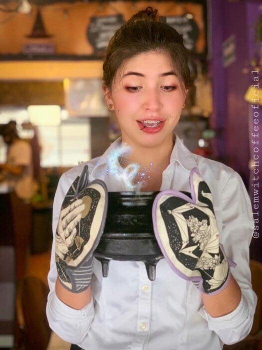 chica sosteniendo un caldero ;Esta cafetería inspirada en brujas sirve las mejores posiciones del mundo oscuro