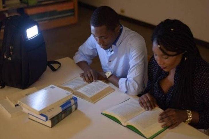 Mike Bellot estudiando junto a una amiga mientras usan su mochila con paneles solares