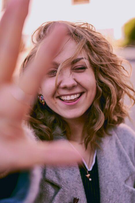 Chica sonriendo y enfocando su rostro ;Diseño de sonrisa, el procedimiento dental que las celebridades están amando