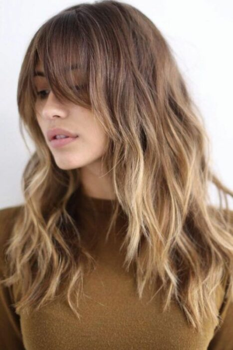 Chica usando un fleco estilo Walft con el cabello largo y teñido de rubio