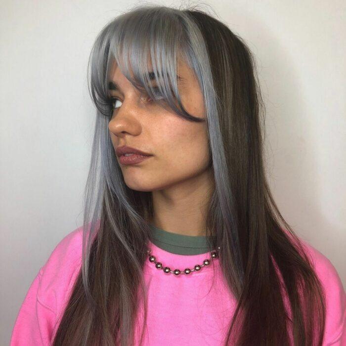 Chica usando un fleco estilo Walft con el cabello largo y teñido de gris con negro