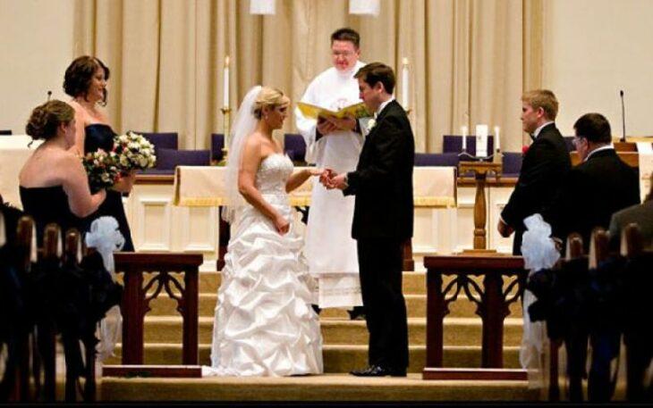 Pareja de novios frente al altar poniéndose los anillos