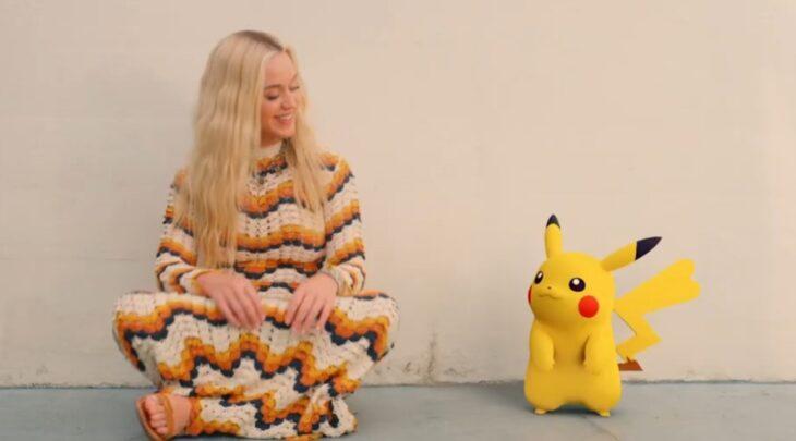 Katy Perry sentada junto a una animación de Pikachu