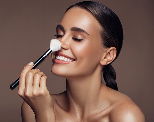 Mujer maquillando su cara y sonriendo