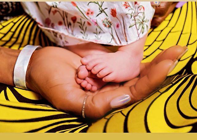 Naomi Campbell sosteniendo los pies de su bebé en una imagen de instagram
