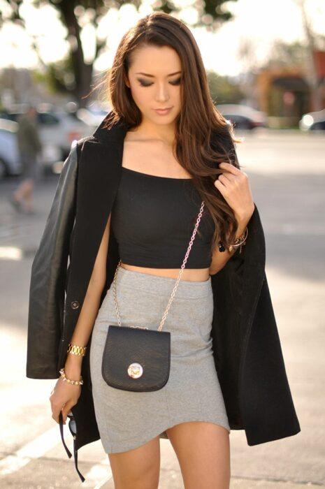 Chica posando para una fotografía mientras usa un bolso pequeñito