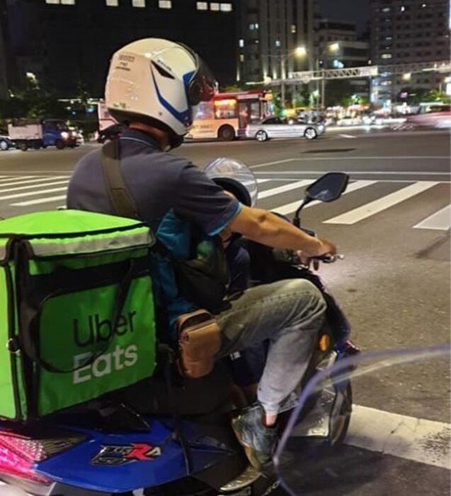 Padre e hijo repartiendo comida en una motocicleta