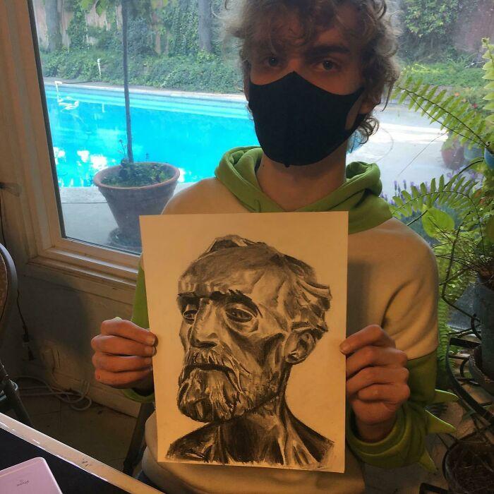 Niño dibujando un anciano con la técnica del carbón