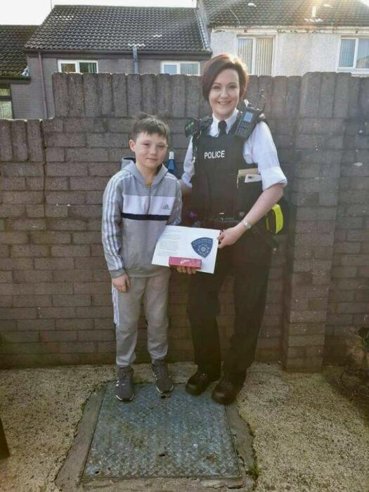 Mujer policía entregando un reconocimiento a un niño