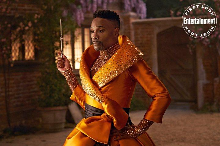 Billy Porter usando un traje de color naranja para ser la nueva hada madrina de Cenicienta
