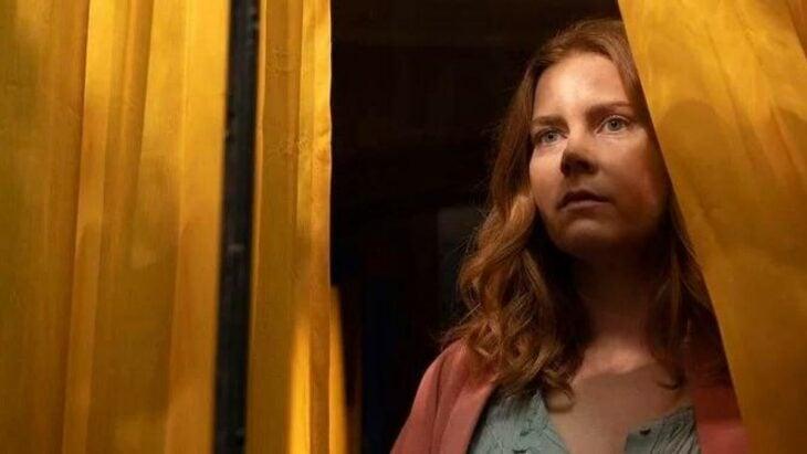 Escena de la película La mujer en la ventana. Ammy Adams parada frente a la ventana