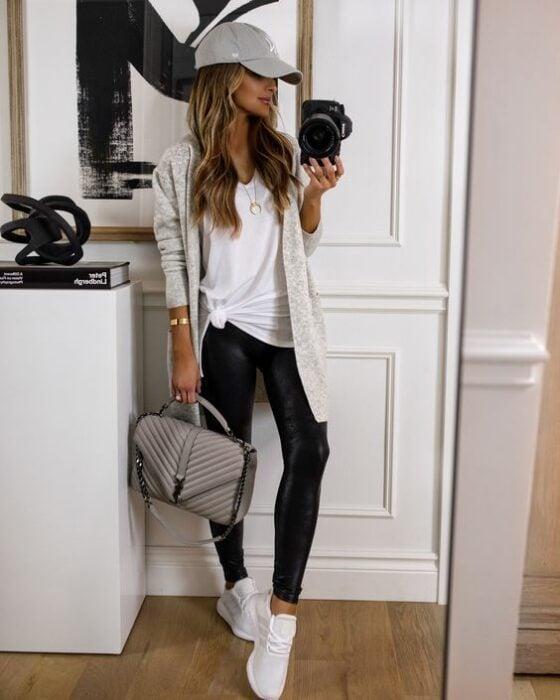 Chica usando leggins, tenis y un cardigan con blusa blanca