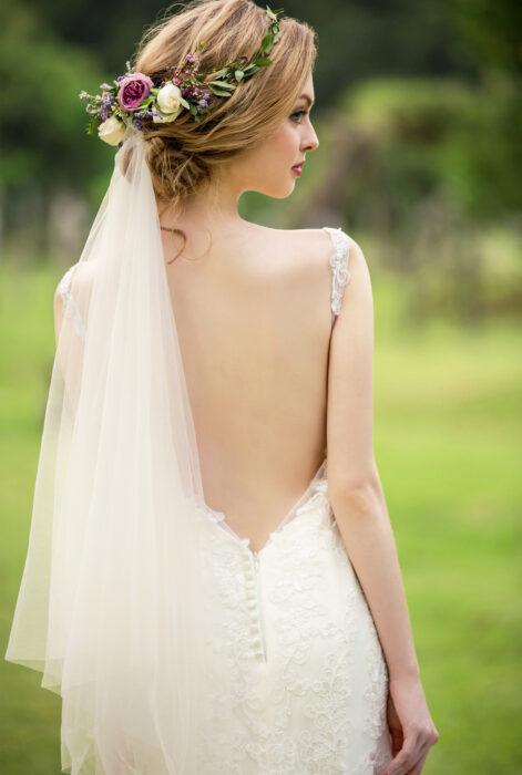Novia usando un vestido escotado con un velo liso