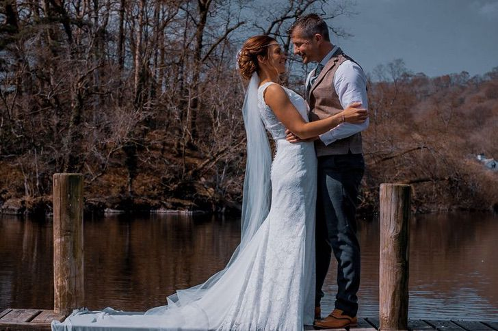 Pareja frente a un lago vestidos de novios mientras se casan