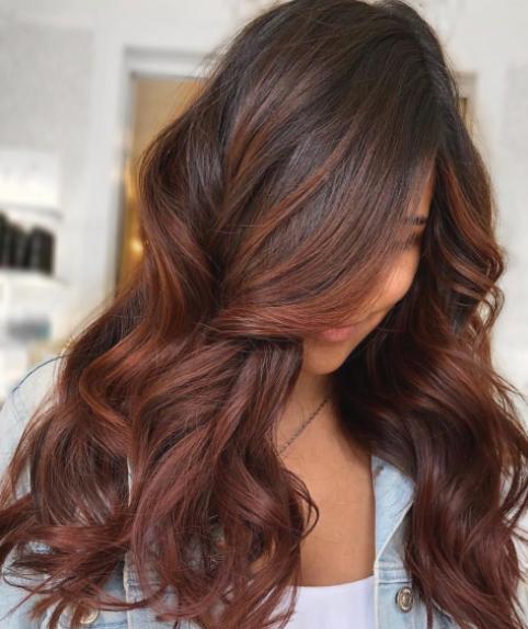 Chica con el cabello teñido en color chocolate con reflejos rojos