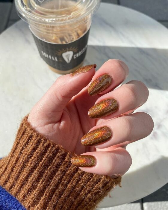 Chica con unas uñas holográficas en tonos cafés