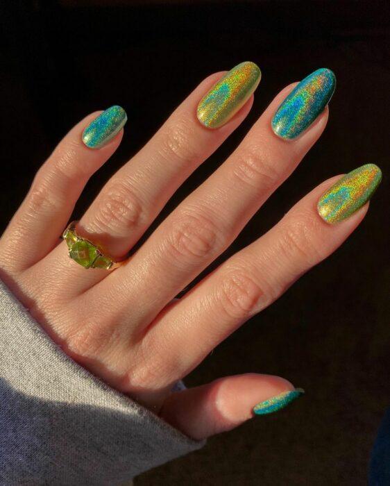 Chica con unas uñas holográficas en tonos verdes