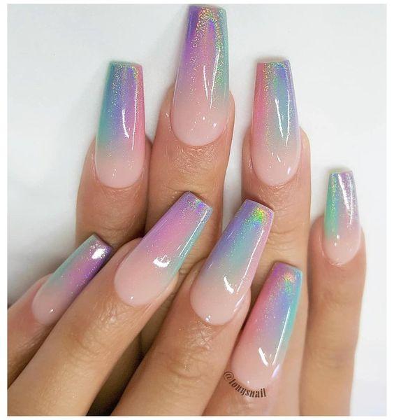 Chica con unas uñas holográficas en tonos rosados