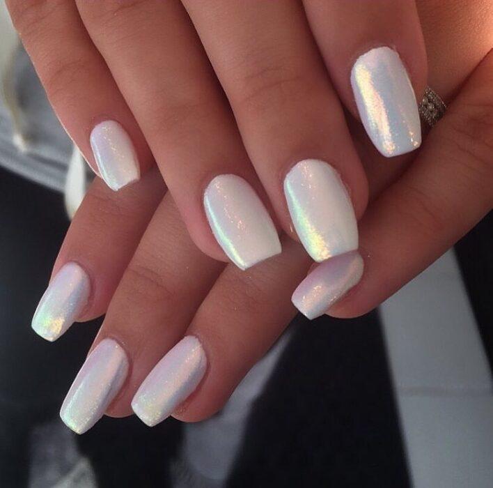 Chica con unas uñas holográficas en tonos rosados con blanco