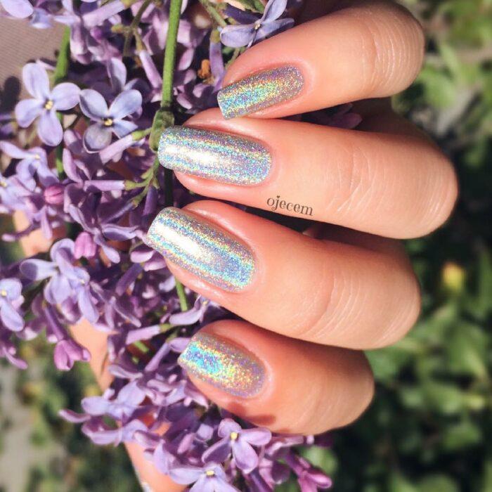 Chica con unas uñas holográficas en tonos plateados