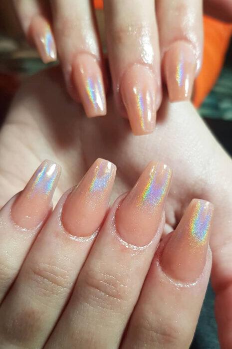 Chica con unas uñas holográficas en tonos nude con plateado