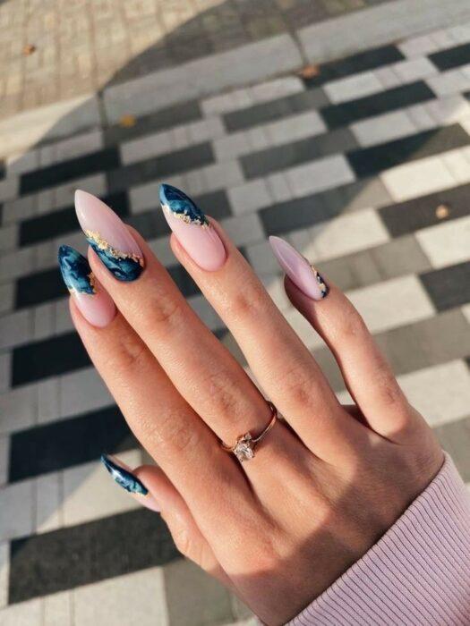 Chica con unas uñas estilo mármol con diferentes colores