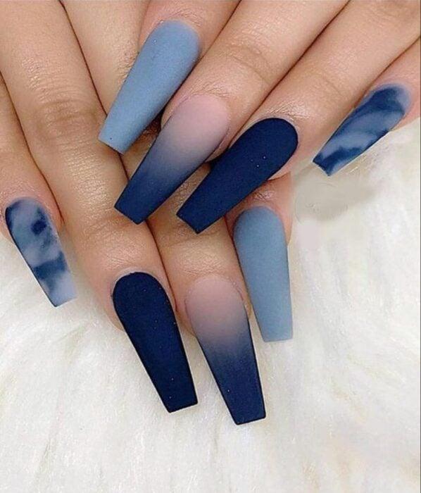 Chica con unas uñas extra largas con diseño ombré en color azul