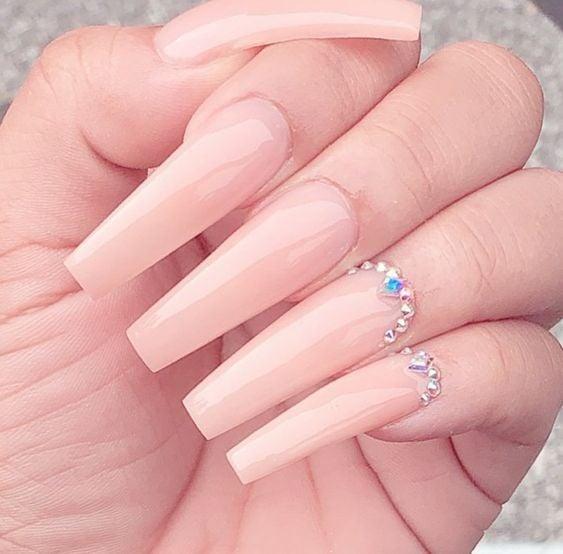 Chica con unas uñas extra largas con diseño en color nude con pedrería